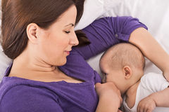 Mãe feliz de sorriso que amamenta seu infante do bebê Foto de Stock Royalty Free