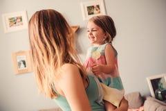 Mãe feliz e filha que têm o divertimento em casa Fotografia de Stock