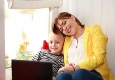 Mãe feliz e filho que olham o portátil em casa Imagens de Stock Royalty Free