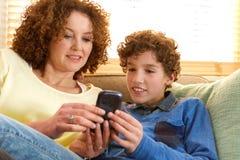 Mãe feliz e filho que sentam-se no sofá em casa Fotos de Stock