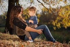 Mãe feliz que joga com seu filho exterior no outono Imagens de Stock