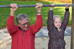 Me and grandpa. Cute little girl tries doing exercises at a horizontal bar together with her grandpa royalty free stock image