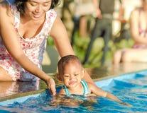 A mãe incentiva a criança que tem o divertimento na piscina Imagem de Stock Royalty Free