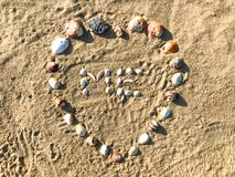 Me letters made in heart shape of Seashells on the sand beach. royalty free stock photography