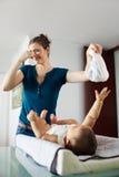 A mãe muda o tecido sujo à filha pequena em casa Foto de Stock Royalty Free