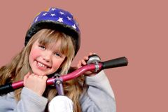 Me and my bike. 6 Year old girl with her pink/purple bike and a safety helmet Royalty Free Stock Photography