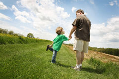 Me and my Dad. A father and son walking in a field Stock Photography