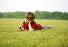 Me & my mp3. A child sitting outside inn the green grass listening to music with an mp3 and headphones stock images