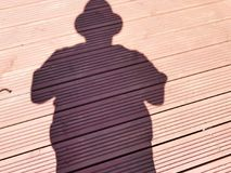 Me and my shadow. A shadow of a man with a cap set on a wooden background Royalty Free Stock Photography