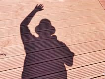 Me and my shadow. A shadow of a man  waving,with a cap on  set on a wooden background Stock Image