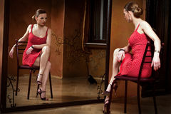 Me and Myself. Beautiful blond in a red dress looking at the mirror. Focus on the woman's reflection. Please see more images from the same shoot Stock Photo