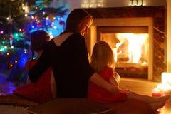 Mãe nova e filhas que sentam-se por uma chaminé no Natal Fotos de Stock Royalty Free