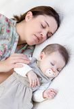 Mãe nova e seu bebê que dormem na cama Foto de Stock Royalty Free