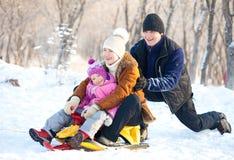 A mãe, o pai e a criança em um inverno estacionam Foto de Stock Royalty Free