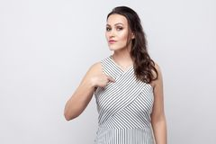 This is me. portrait of proud beautiful young brunette woman with striped dress standing, looking at camera with serious face and. Pointing herself. indoor stock image