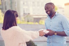 Positive young woman taking a present. This is for me. Positive nice young women looking at her boyfriend and taking her present while having a date with him Stock Images