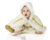 Me?  ...a Princess?. An adorable baby `snow princess` reaching for her wand while looking up questioningly.  On a white background Royalty Free Stock Photo