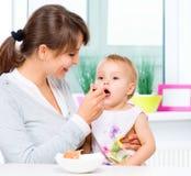 Mãe que alimenta seu bebê Imagem de Stock