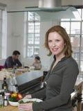 Mãe que prepara a salada com a família que senta-se no fundo Imagens de Stock Royalty Free