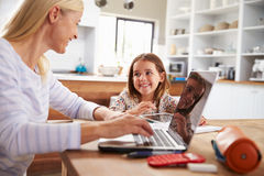 Mãe que usa o laptop com sua filha nova Fotos de Stock Royalty Free