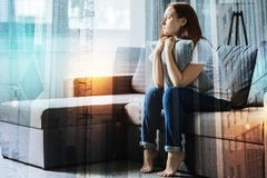 Calm upset woman hugging a pillow and looking aside. Me and silence. Calm upset pretty woman sitting in the empty room hugging a pillow and looking aside royalty free stock photo