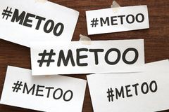 Me Too hashtag word on white papers on wood.  Me Too social movement hashtag against sexual assault and harassment. Me Too hashtag word on white papers on wood Stock Images