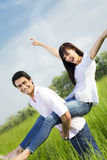 Meadow. Man giving woman piggyback in meadow, laughing. Narrow focus on his eye Stock Images