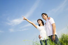 Meadow. Young couple in meadow with hand in air, hugging and smiling. Copy space Royalty Free Stock Photos