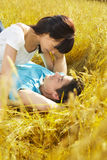 Meadow. Young couple laying down in meadow and hugging Stock Photography