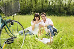 Meadow. Couple having a picnic in a park, smiling and looking at the camera Royalty Free Stock Photo