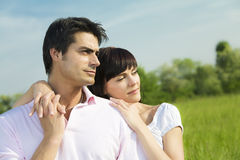 Meadow. Couple standing in meadow, arm around and looking away. Copy space Stock Photo