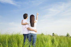 Meadow. Young couple in meadow with hand in air, hugging. Copy space Stock Photos