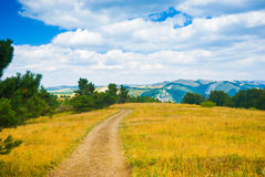 Meadow. Country road through a meadow in Crimea mountains Royalty Free Stock Photo