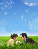 Meadow. Wedding couple lying on summer meadow over romantic soap bubbles Royalty Free Stock Photography