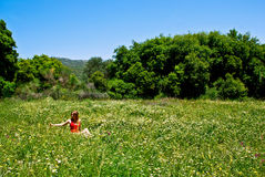 Meadow. Young girl sitting at a flower meadow Royalty Free Stock Photos