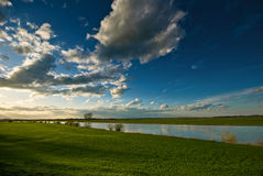 Meadow and a blue sky. On this picture you can see a landscape consisting of a meadow, a river and a sky with some clouds Stock Photography