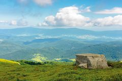 Meadow with boulders in Carpathian mountains in su. Landscape with grassy meadow with giant boulders on the slope of a hill in Carpathian mountain ridge on a royalty free stock image