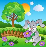 Meadow with bunny holding flower Royalty Free Stock Images