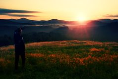 Meadow colorful sunrise with dark  man silhouette Stock Photography