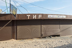 Meadow covered pavilion with a broken roller shutters and the signboard Tir, sanded in the offseason Stock Photography