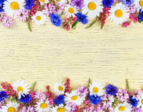 Meadow flowers on yellow rustic wooden background. Stock Photo