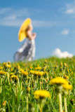 Meadow in focus and blurred girl. Young girl with yellow parasol a meadow in spring. Focus is on dandelions, girl is blurred stock images
