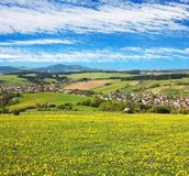 Meadow ful of dandelions and beautiful clouds. Panoramic view of Horni Lidec village with meadow ful of dandelions and beautiful clouds - Carpathiam mountains Royalty Free Stock Photography