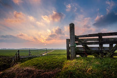 Meadow Gates. A rural scene with a meadow, a fence and a sunset Royalty Free Stock Photo