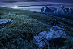 Meadow with huge stones on top of mountain range at night stock photography