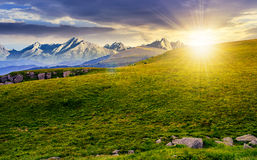 Meadow with huge stones on top of mountain range at sunset Stock Photos