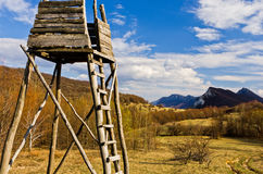 Meadow with hunting watchtower with mountain peaks in background,  Homolje mountains landscape on a sunny day in early spring Stock Photo