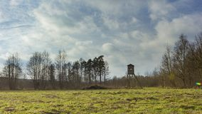 Meadow landscape with raised hide. And trees under beautiful cloudy sky Royalty Free Stock Photography