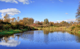 Meadow landscape of a river to a lake Royalty Free Stock Photo