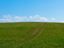 Meadow meets sky. Green meadow meets blue sky with white clouds Stock Images